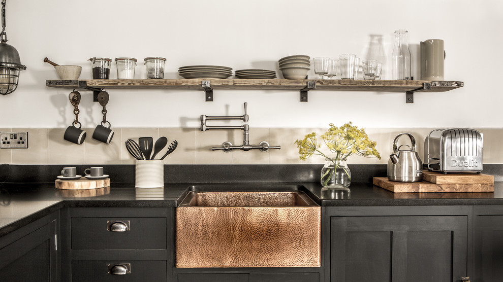 Kitchen - small industrial l-shaped kitchen idea in Cornwall with a farmhouse sink, black cabinets, granite countertops, cement tile backsplash and open cabinets