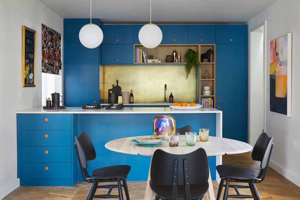 Eat-in kitchen - mid-sized contemporary single-wall medium tone wood floor and brown floor eat-in kitchen idea in London with an undermount sink, flat-panel cabinets, blue cabinets, solid surface countertops, metallic backsplash, metal backsplash, black appliances, white countertops and a peninsula