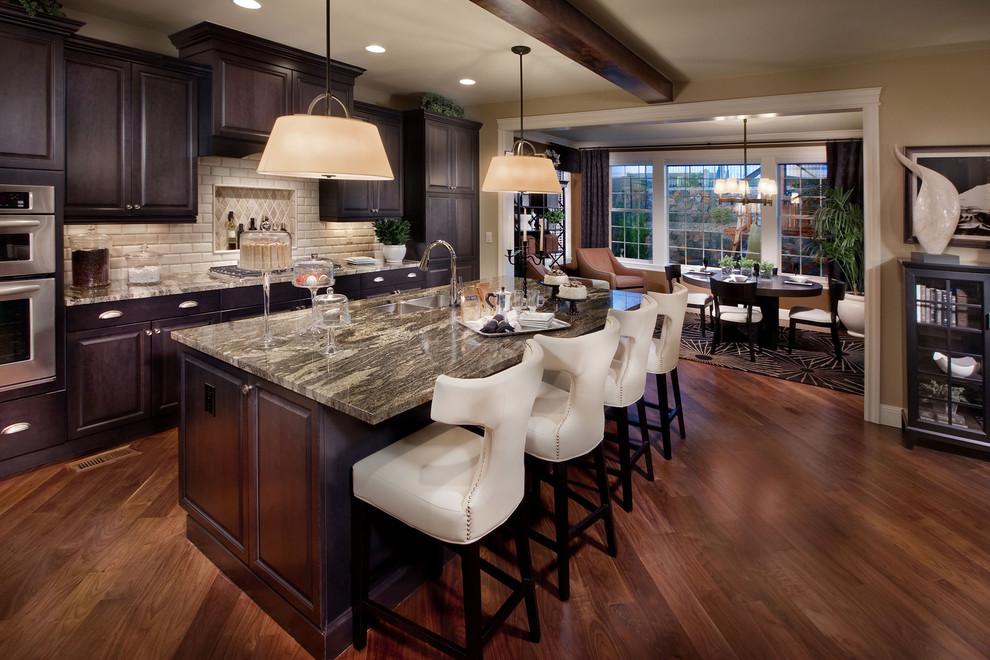 Example of a tuscan eat-in kitchen design in Denver with a double-bowl sink, raised-panel cabinets, dark wood cabinets, beige backsplash and subway tile backsplash
