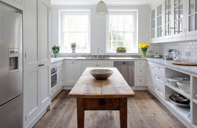 Photo of a traditional u-shaped enclosed kitchen in Wiltshire with recessed-panel cabinets, white cabinets, marble worktops, white splashback, metro tiled splashback and stainless steel appliances.