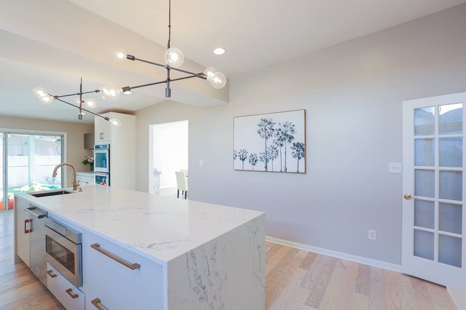 Large trendy l-shaped light wood floor and beige floor enclosed kitchen photo in Baltimore with an undermount sink, flat-panel cabinets, white cabinets, marble countertops, gray backsplash, ceramic backsplash, stainless steel appliances, an island and white countertops