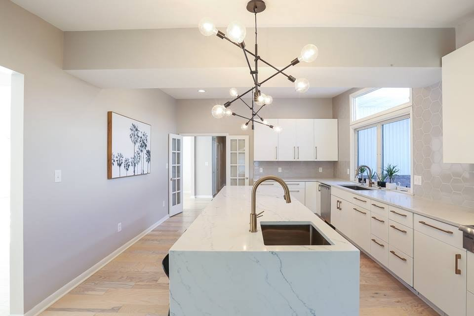 Example of a large trendy l-shaped light wood floor and beige floor enclosed kitchen design in Baltimore with an undermount sink, flat-panel cabinets, white cabinets, marble countertops, gray backsplash, ceramic backsplash, stainless steel appliances, an island and white countertops