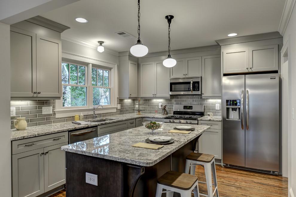 Small elegant l-shaped medium tone wood floor kitchen photo in Atlanta with an undermount sink, shaker cabinets, gray cabinets, granite countertops, gray backsplash, ceramic backsplash, stainless steel appliances and an island