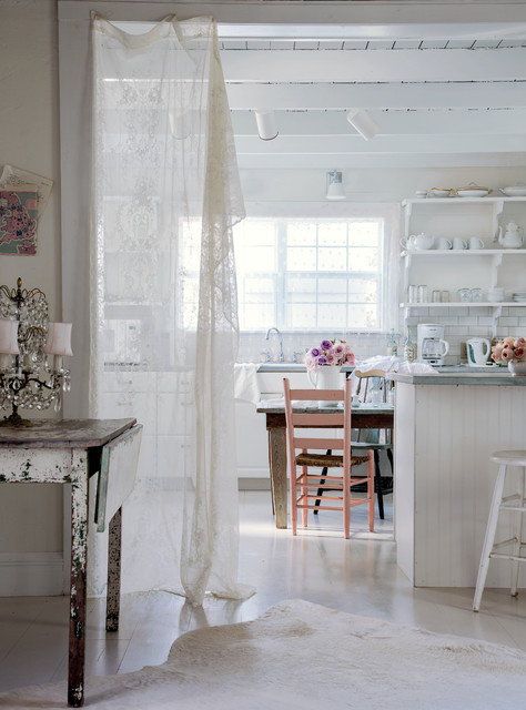 A white Shabby Chic kitchen with vintage furniture, beadboard, and open shelves