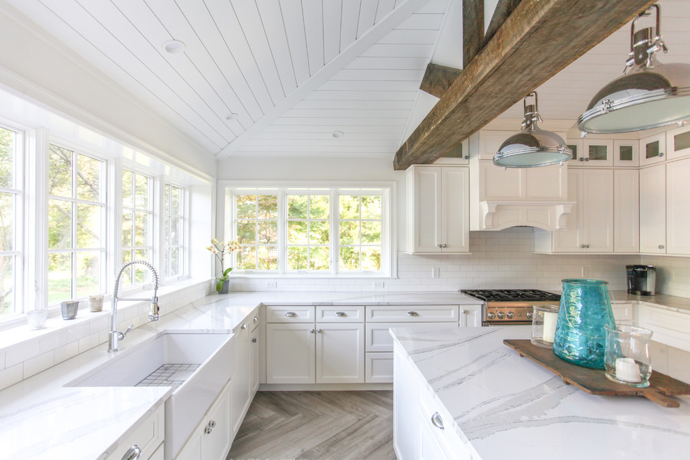 Inspiration for a large coastal u-shaped porcelain tile and gray floor eat-in kitchen remodel in New York with a farmhouse sink, shaker cabinets, white cabinets, quartz countertops, white backsplash, subway tile backsplash, paneled appliances, an island and white countertops