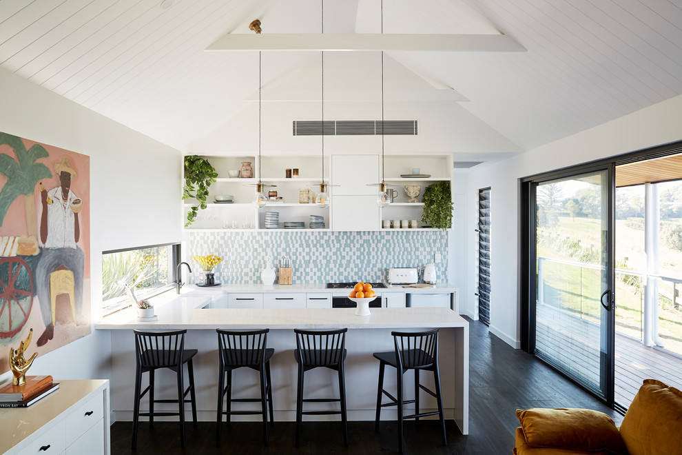 Open concept kitchen - coastal u-shaped dark wood floor and black floor open concept kitchen idea in Other with a farmhouse sink, flat-panel cabinets, white cabinets, multicolored backsplash, paneled appliances, a peninsula and white countertops