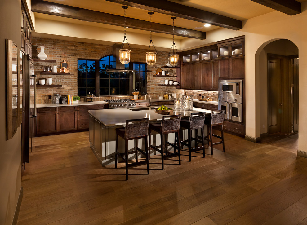 Large tuscan medium tone wood floor and brown floor kitchen photo in Tampa with solid surface countertops, brick backsplash, stainless steel appliances, an island, an undermount sink, shaker cabinets and dark wood cabinets