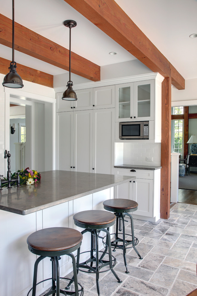Example of a large classic u-shaped travertine floor eat-in kitchen design in Manchester with stainless steel appliances, limestone countertops, an undermount sink, shaker cabinets, white cabinets, white backsplash, subway tile backsplash and an island
