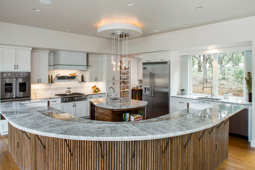 Inspiration for a large transitional l-shaped medium tone wood floor and beige floor enclosed kitchen remodel in Austin with an undermount sink, shaker cabinets, white cabinets, white backsplash, matchstick tile backsplash, stainless steel appliances and two islands