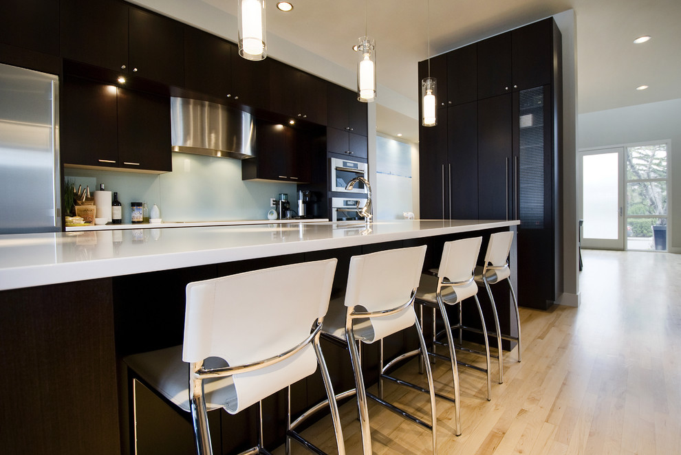 Trendy kitchen photo in Calgary with flat-panel cabinets, dark wood cabinets and glass sheet backsplash