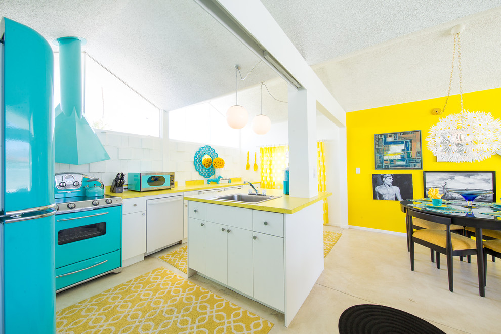 Inspiration for a mid-century modern beige floor eat-in kitchen remodel in San Diego with a drop-in sink, flat-panel cabinets, white cabinets, white backsplash, colored appliances, an island and yellow countertops