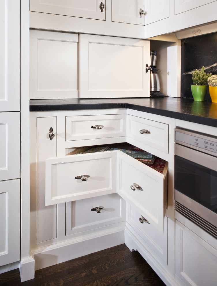 Inspiration for a large timeless l-shaped dark wood floor kitchen remodel in Minneapolis with recessed-panel cabinets, white cabinets, soapstone countertops, black backsplash, stone slab backsplash, black appliances and an island