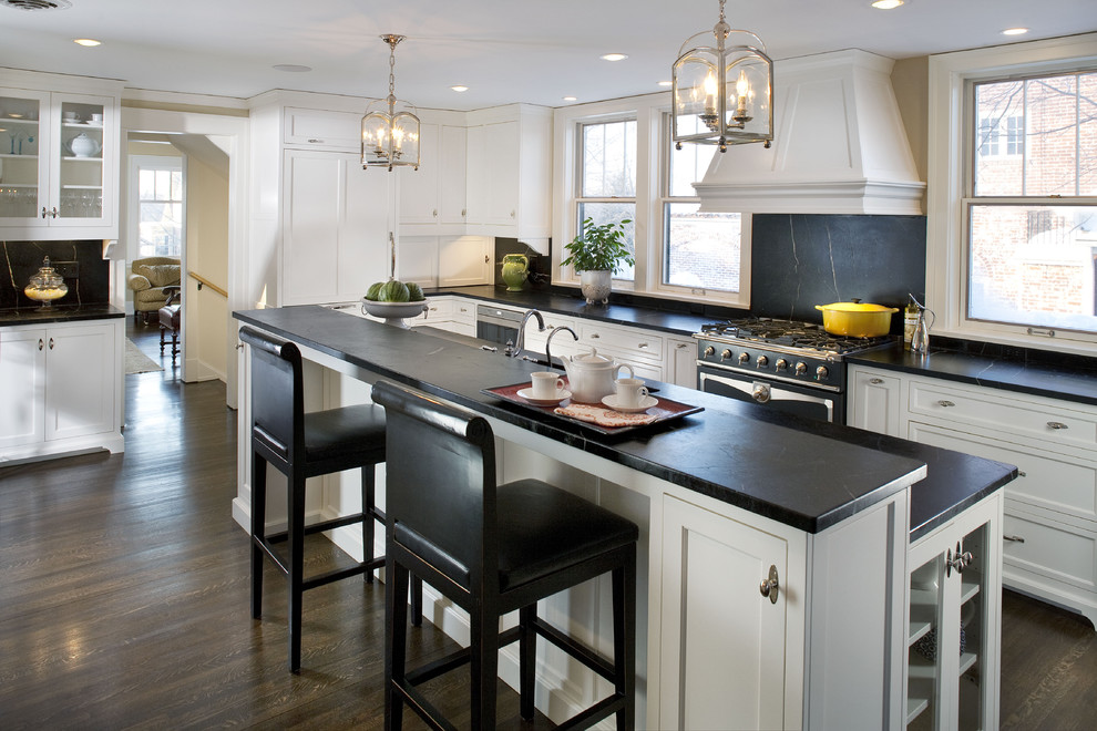 Example of a large classic l-shaped dark wood floor kitchen design in Minneapolis with recessed-panel cabinets, white cabinets, soapstone countertops, black backsplash, stone slab backsplash, black appliances and an island