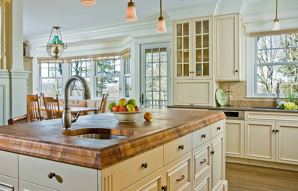 Example of a classic kitchen design in Boston with wood countertops, an undermount sink and beige cabinets