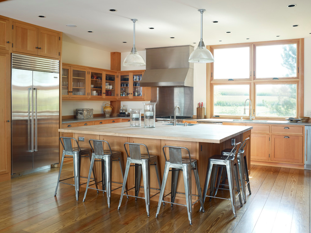 Inspiration for a farmhouse kitchen remodel in Milwaukee with glass-front cabinets, stainless steel appliances, wood countertops and medium tone wood cabinets
