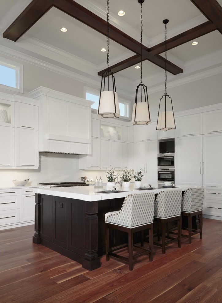Large transitional l-shaped brown floor and dark wood floor eat-in kitchen photo in Miami with shaker cabinets, white cabinets, white backsplash, stainless steel appliances, an island and quartzite countertops