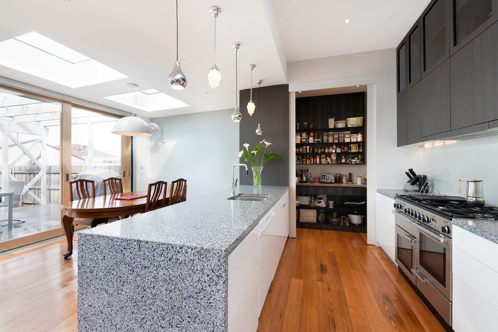 Inspiration for a contemporary galley eat-in kitchen remodel in Melbourne with a double-bowl sink, flat-panel cabinets, white cabinets, white backsplash, glass sheet backsplash and stainless steel appliances