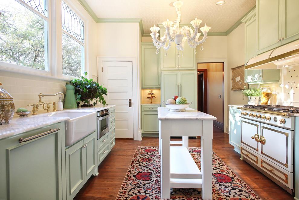 Example of an ornate u-shaped medium tone wood floor enclosed kitchen design in Portland with a farmhouse sink, green cabinets, recessed-panel cabinets, quartz countertops, beige backsplash, ceramic backsplash and an island