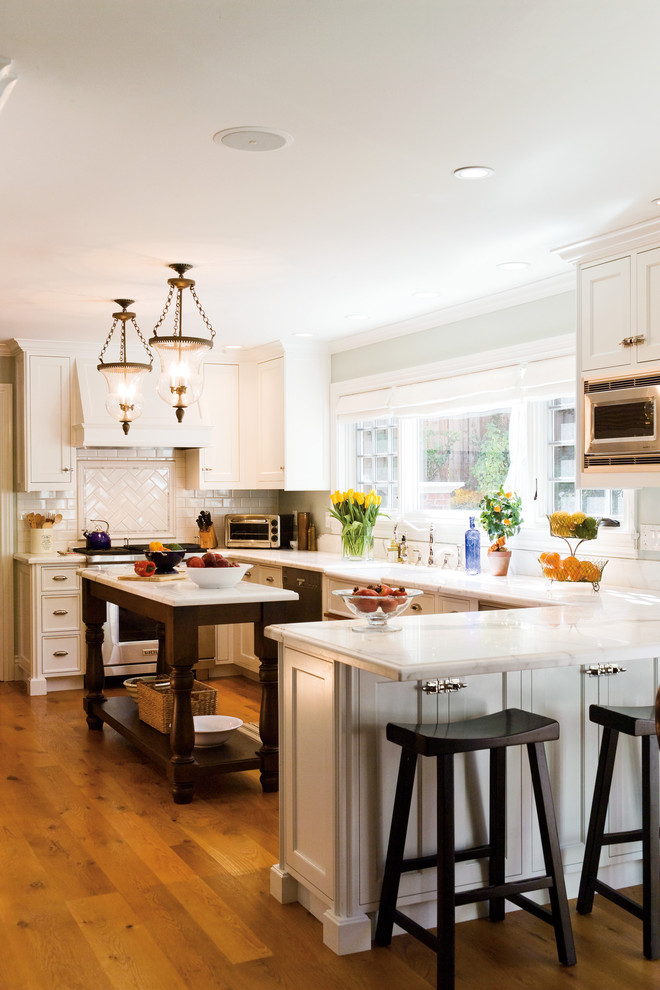 Mid-sized elegant u-shaped medium tone wood floor eat-in kitchen photo in San Francisco with ceramic backsplash, white cabinets, white backsplash, stainless steel appliances, marble countertops, an island, a farmhouse sink and shaker cabinets