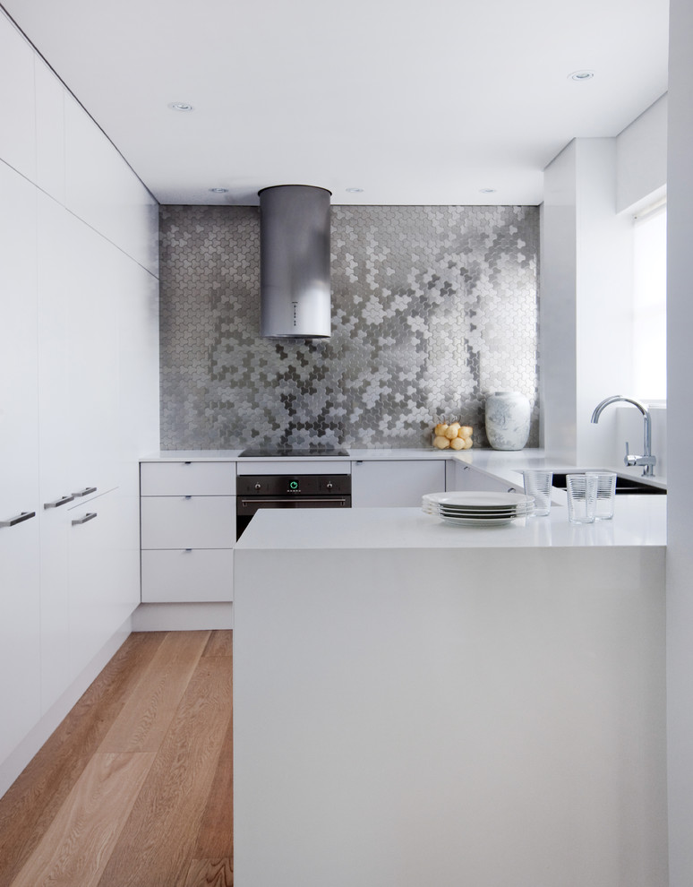 Inspiration for a small contemporary u-shaped medium tone wood floor eat-in kitchen remodel in Sydney with metal backsplash, black appliances, a drop-in sink, flat-panel cabinets, white cabinets and quartz countertops