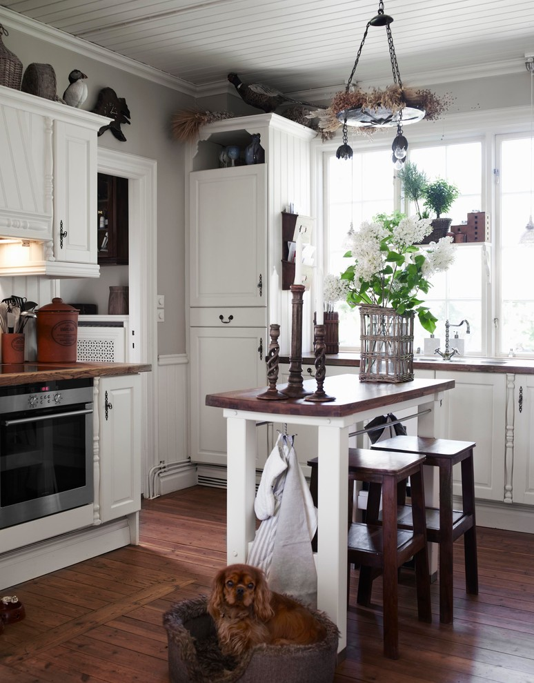 Inspiration for a mid-sized eclectic single-wall dark wood floor eat-in kitchen remodel in Stockholm with raised-panel cabinets, white cabinets, stainless steel appliances, an island and wood countertops