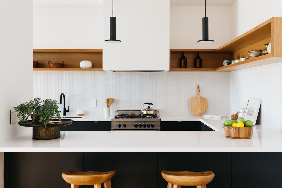 Mid-sized trendy u-shaped light wood floor eat-in kitchen photo in Los Angeles with an undermount sink, flat-panel cabinets, black cabinets, quartzite countertops, white backsplash, mosaic tile backsplash, stainless steel appliances and a peninsula