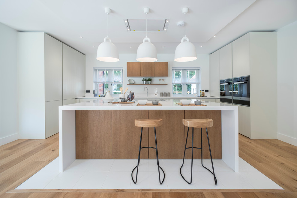 Kitchen - contemporary u-shaped medium tone wood floor and brown floor kitchen idea in Dorset with flat-panel cabinets, white cabinets and an island