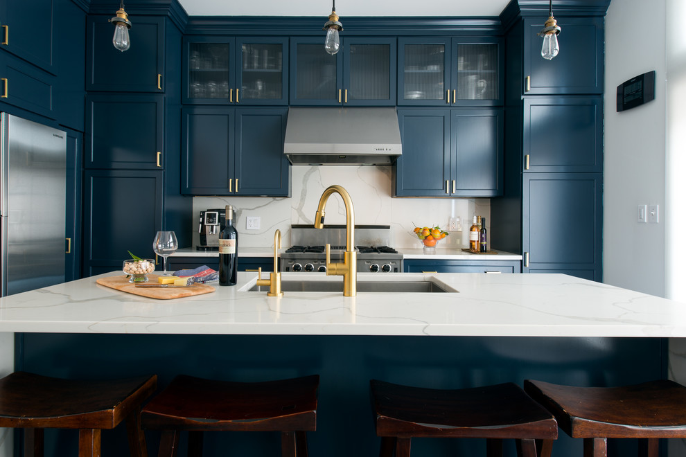 Inspiration for a transitional l-shaped eat-in kitchen remodel in Chicago with an undermount sink, shaker cabinets, blue cabinets, quartz countertops, gray backsplash, stone slab backsplash, stainless steel appliances and an island
