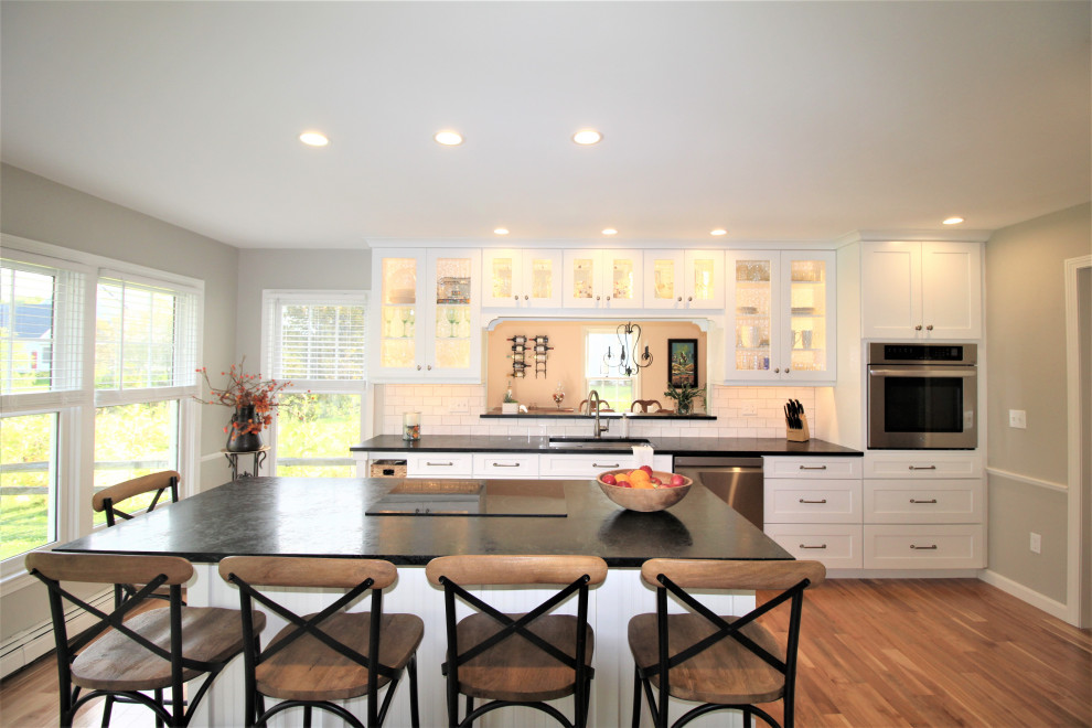 Example of a large classic galley medium tone wood floor and brown floor eat-in kitchen design in Burlington with an undermount sink, shaker cabinets, white cabinets, soapstone countertops, white backsplash, subway tile backsplash, stainless steel appliances, an island and green countertops