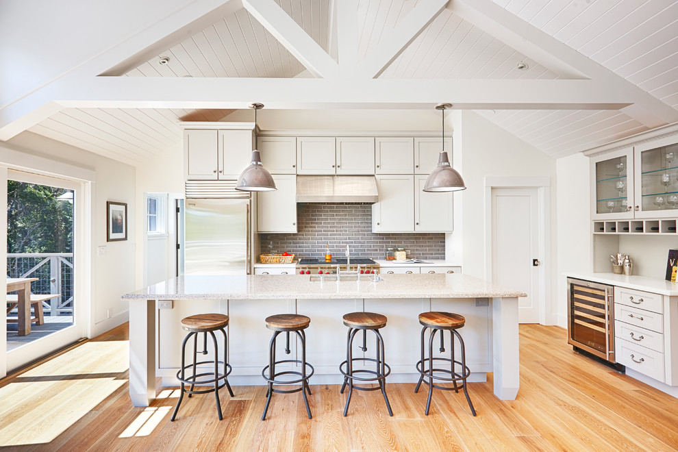 Large farmhouse galley medium tone wood floor kitchen photo in San Francisco with an undermount sink, shaker cabinets, white cabinets, granite countertops, gray backsplash, glass tile backsplash, stainless steel appliances and an island