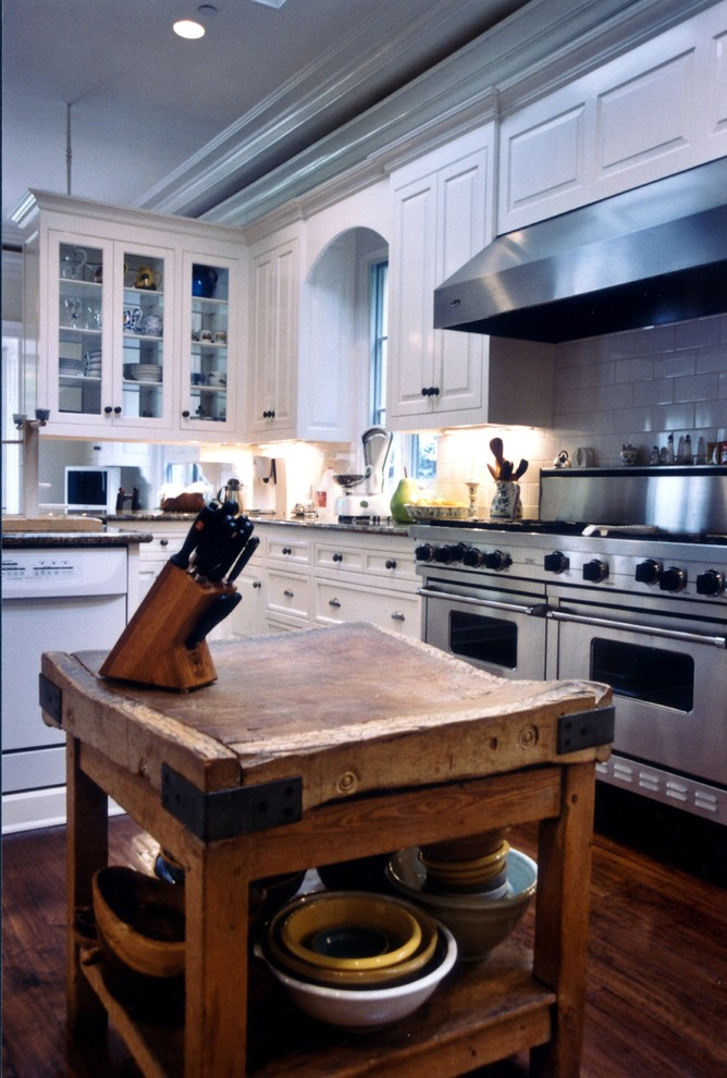 Huge elegant u-shaped medium tone wood floor eat-in kitchen photo in Los Angeles with a drop-in sink, recessed-panel cabinets, white cabinets, granite countertops, white backsplash, subway tile backsplash, stainless steel appliances and an island