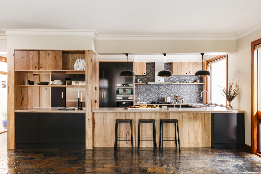 Large minimalist u-shaped slate floor and multicolored floor open concept kitchen photo in Adelaide with flat-panel cabinets, medium tone wood cabinets, solid surface countertops, gray backsplash, ceramic backsplash, stainless steel appliances and an island