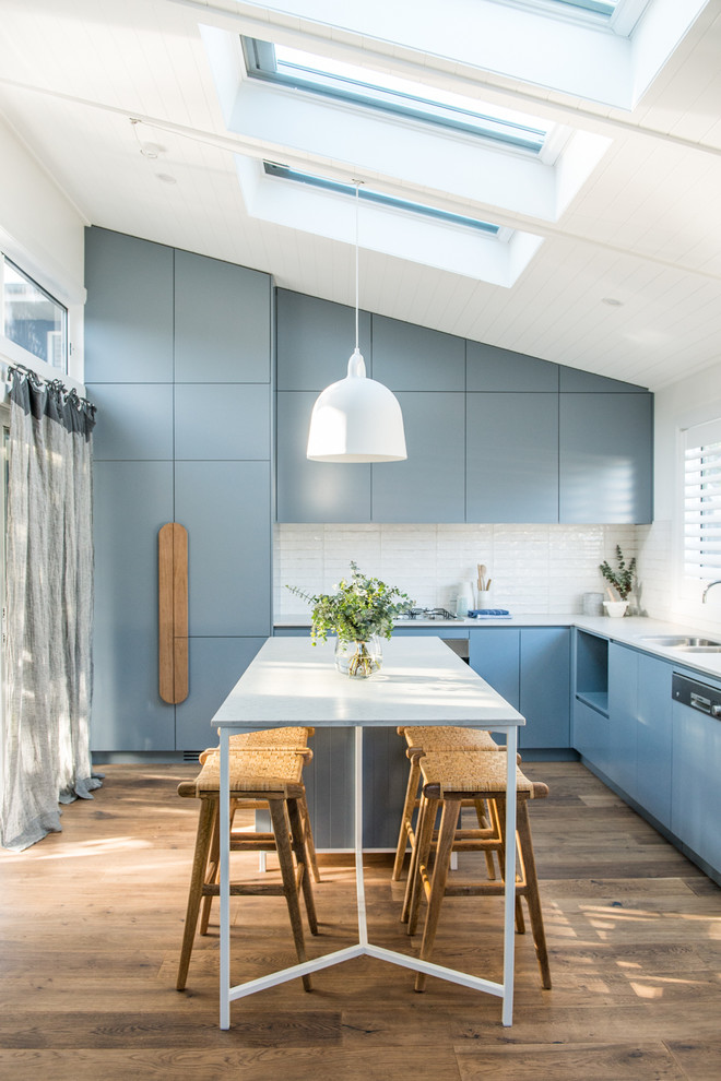 Example of a beach style dark wood floor kitchen design in Sydney with flat-panel cabinets, blue cabinets, white backsplash, paneled appliances and an island