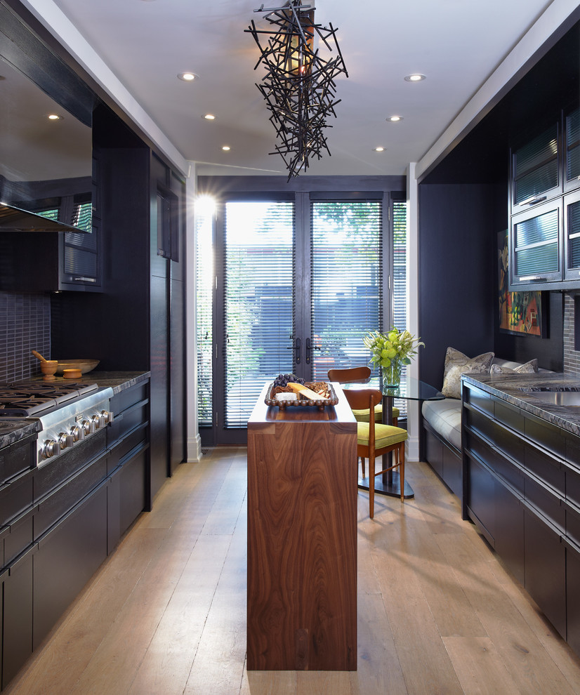 Eat-in kitchen - contemporary eat-in kitchen idea in Toronto with flat-panel cabinets, black cabinets, black backsplash and stainless steel appliances