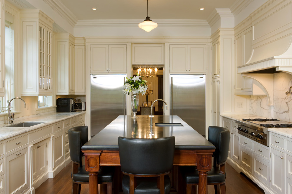 Example of a large classic galley dark wood floor enclosed kitchen design in Toronto with an undermount sink, shaker cabinets, white cabinets, white backsplash, stainless steel appliances, marble countertops, stone slab backsplash and an island