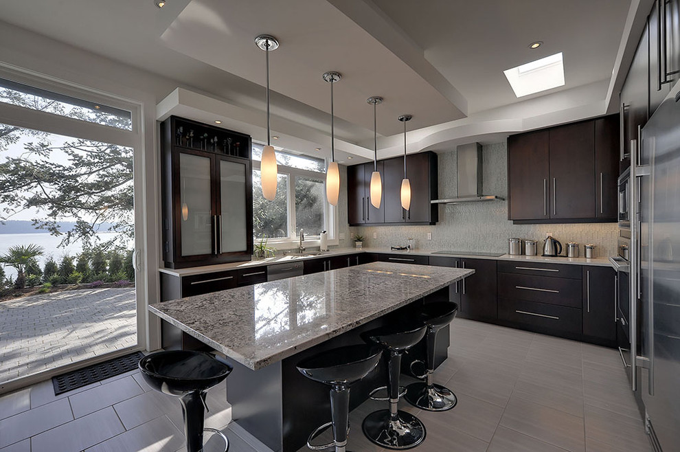Trendy l-shaped kitchen photo in Vancouver with flat-panel cabinets, stainless steel appliances and dark wood cabinets