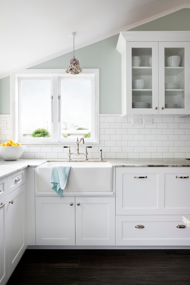 Inspiration for a mid-sized timeless u-shaped porcelain tile kitchen remodel in Auckland with a farmhouse sink, recessed-panel cabinets, white cabinets, granite countertops, white backsplash, stainless steel appliances and subway tile backsplash