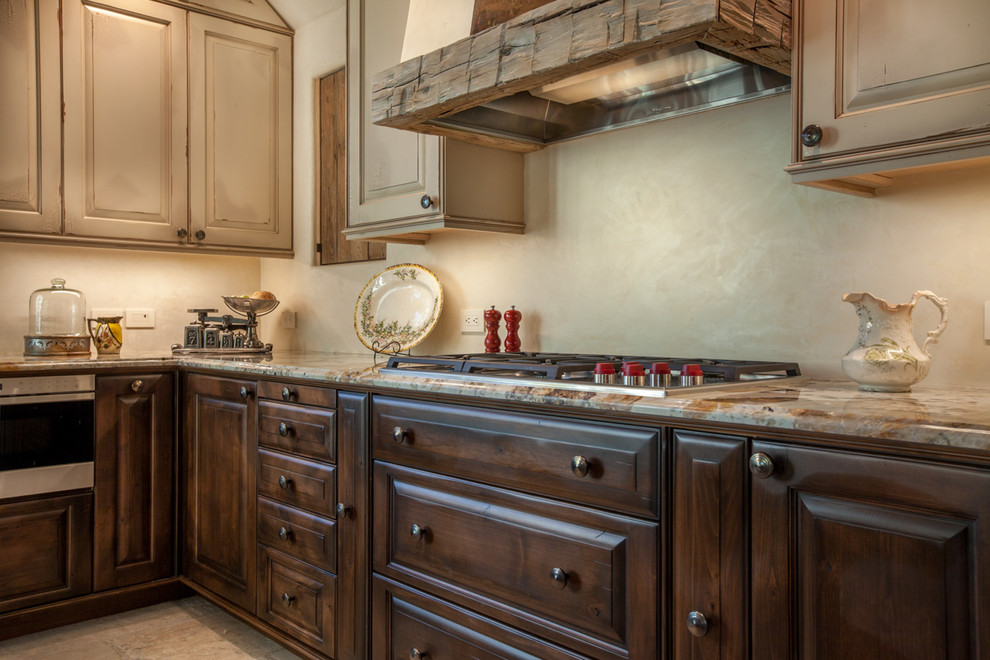 Mid-sized elegant l-shaped ceramic tile open concept kitchen photo in Denver with raised-panel cabinets, paneled appliances, an island, a farmhouse sink, dark wood cabinets and granite countertops