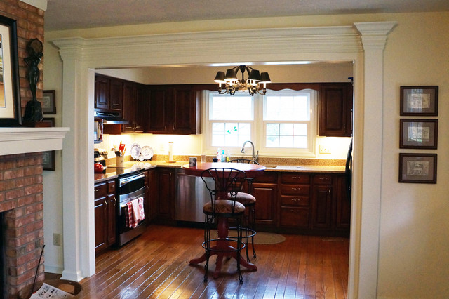 Example of a mid-sized classic u-shaped medium tone wood floor eat-in kitchen design in Indianapolis with an undermount sink, raised-panel cabinets, dark wood cabinets, quartz countertops, white backsplash, stainless steel appliances and no island