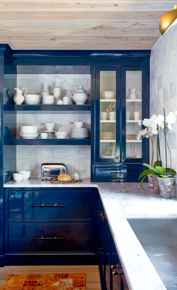 Inspiration for a transitional u-shaped light wood floor kitchen remodel in Atlanta with an undermount sink, recessed-panel cabinets, blue cabinets, marble countertops, white backsplash, stone tile backsplash, stainless steel appliances and an island