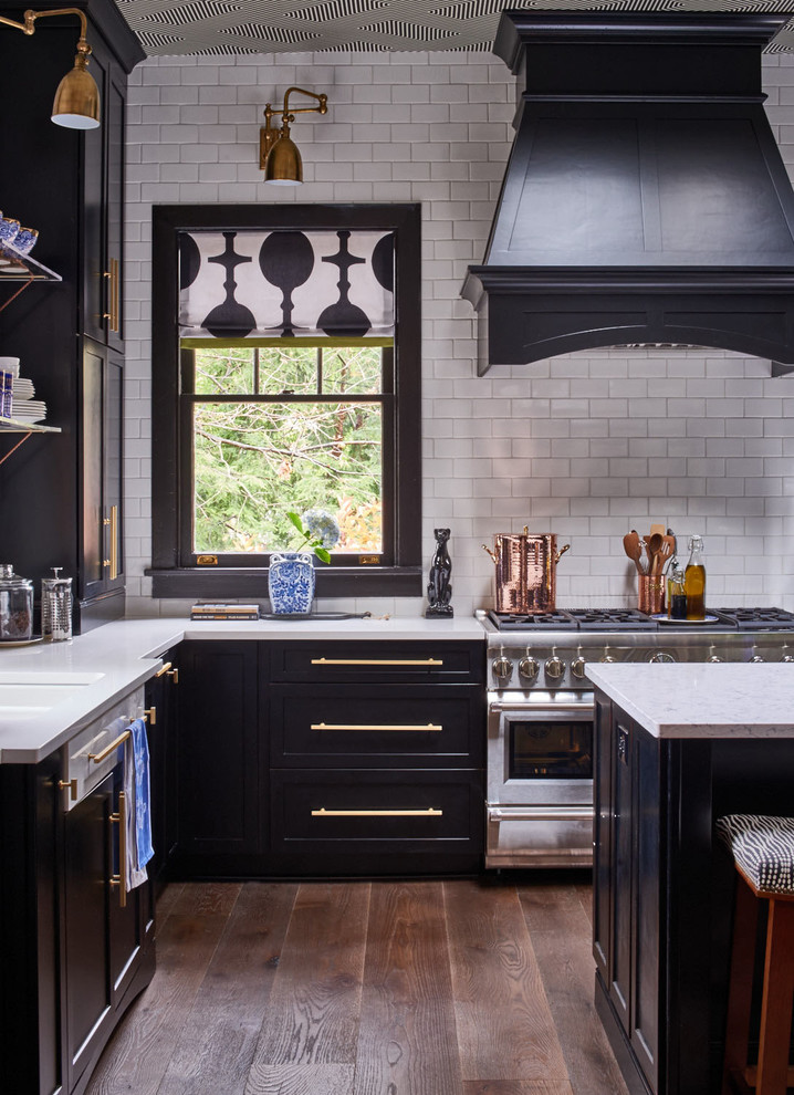 Mid-sized transitional l-shaped medium tone wood floor and brown floor kitchen photo in Raleigh with shaker cabinets, white backsplash, subway tile backsplash, stainless steel appliances, an island, an undermount sink and quartz countertops