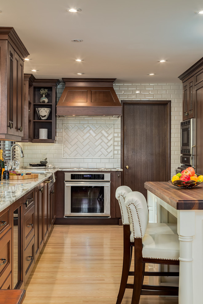 Example of a classic u-shaped light wood floor kitchen design in Calgary with recessed-panel cabinets, dark wood cabinets, white backsplash, subway tile backsplash, stainless steel appliances and an island