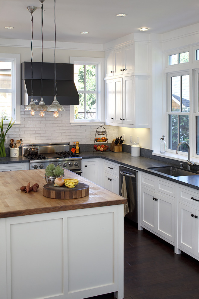 Elegant kitchen photo in San Francisco with stainless steel appliances, subway tile backsplash, wood countertops and white cabinets