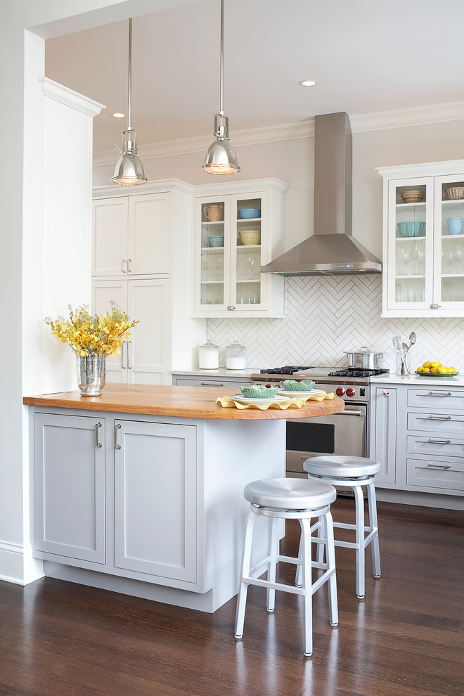 Elegant kitchen photo in Chicago with white cabinets, wood countertops, white backsplash and shaker cabinets