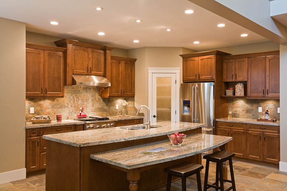 Inspiration for a timeless kitchen remodel in Vancouver with stainless steel appliances, granite countertops, a double-bowl sink, recessed-panel cabinets, medium tone wood cabinets, multicolored backsplash and stone tile backsplash