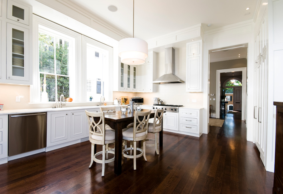 Example of a classic brown floor kitchen design in DC Metro with glass-front cabinets, white cabinets, stainless steel appliances and white countertops