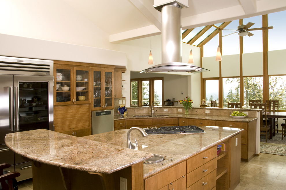 Example of a classic eat-in kitchen design in Denver with flat-panel cabinets, stainless steel appliances, granite countertops, a double-bowl sink and medium tone wood cabinets