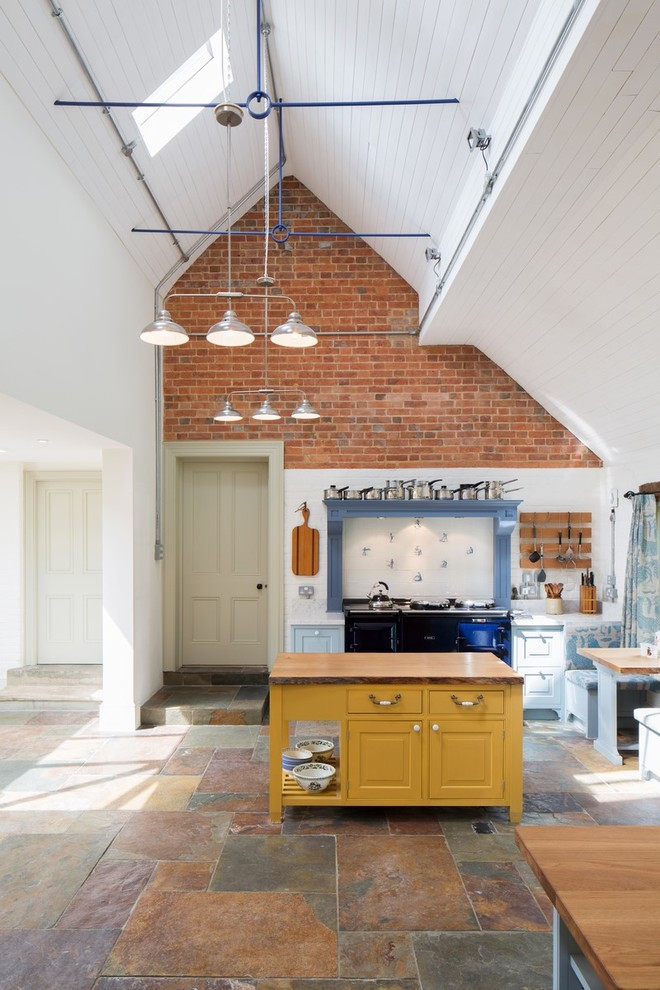 Elegant single-wall slate floor kitchen photo in London with yellow cabinets, wood countertops, white backsplash and an island