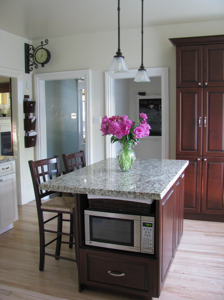 Kitchen - traditional kitchen idea in Toronto with raised-panel cabinets and dark wood cabinets