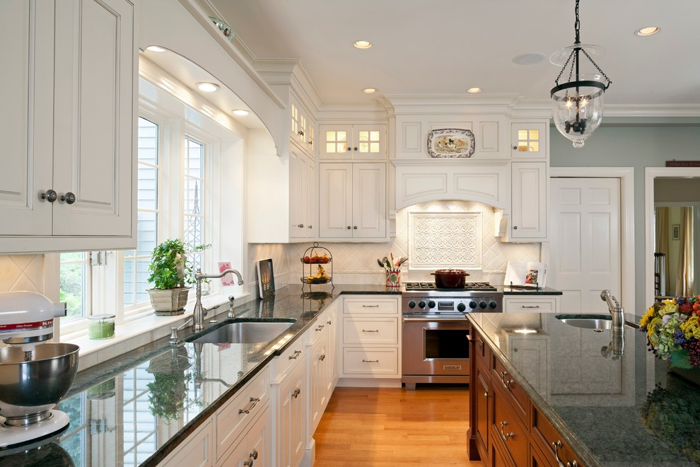 Kitchen - traditional kitchen idea in Boston with an undermount sink, raised-panel cabinets, white cabinets and beige backsplash